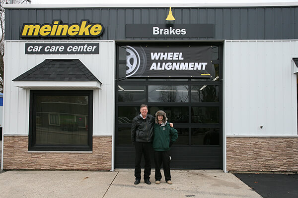 Two men standing outside a Meineke store with a Meineke Car Care Center sign
